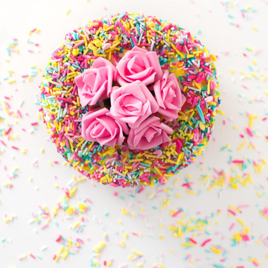 Overhead photo of a cake coated in sprinkles with pink flowers on top.