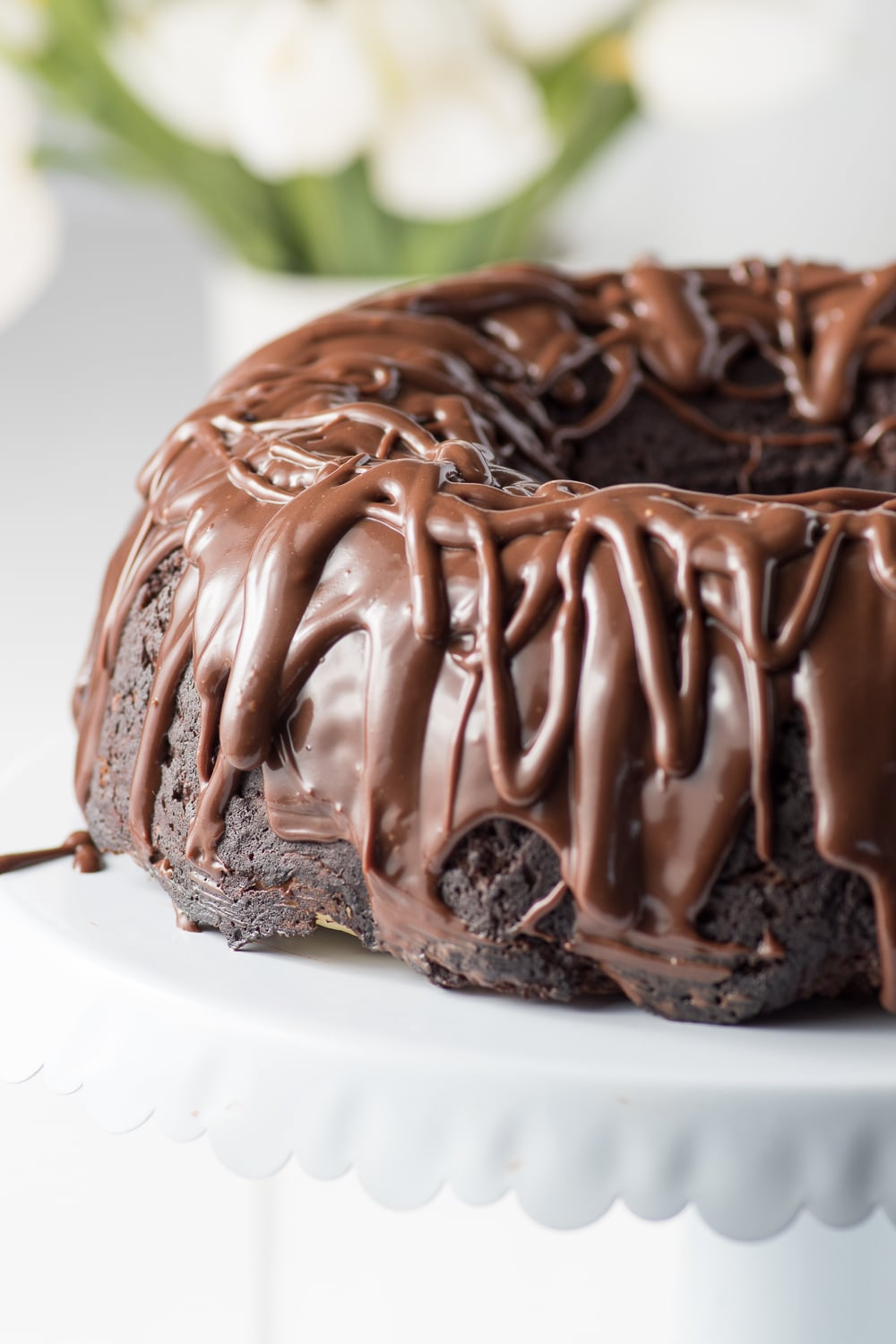 Dark chocolate ganache dripping from a chocolate bundt cake