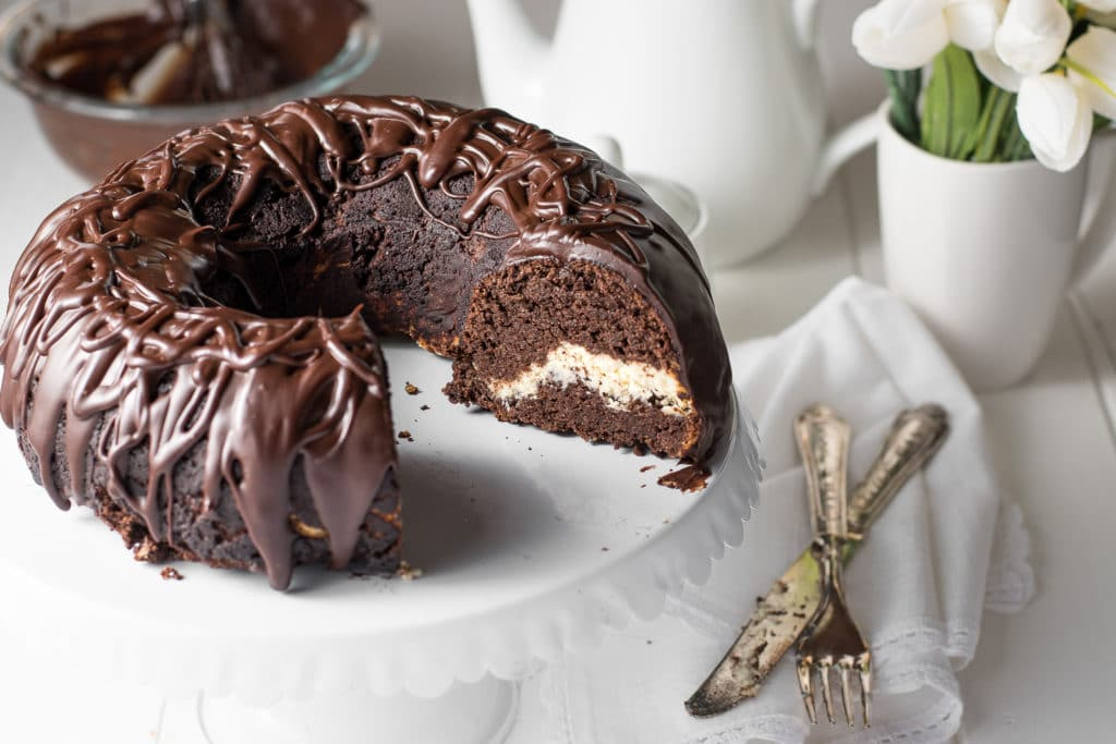 chocolate bundt cake with chocolate ganache on a white cake stand