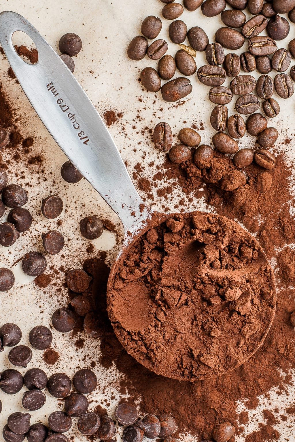 measuring cup with dark cocoa powder surrounded by dark chocolate chips and roasted coffee beans