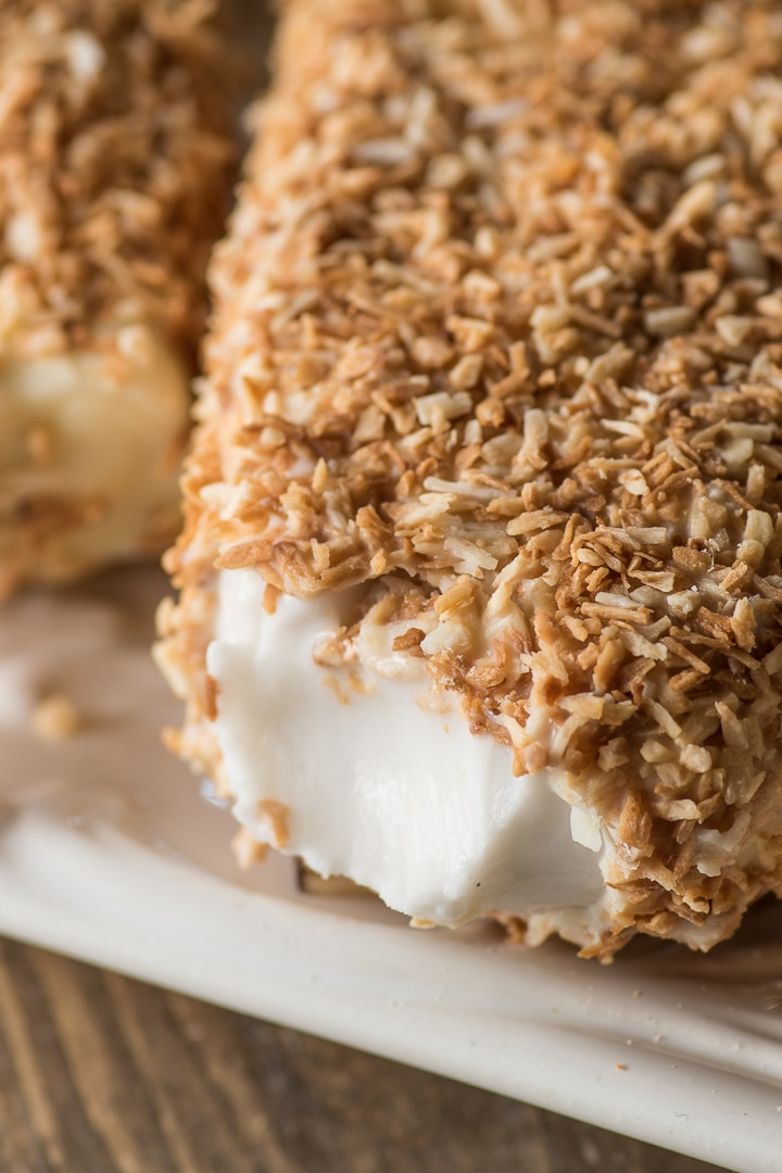 close up shot of the inside of a creamy coconut popsicle surrounded by a toasted coconut shell