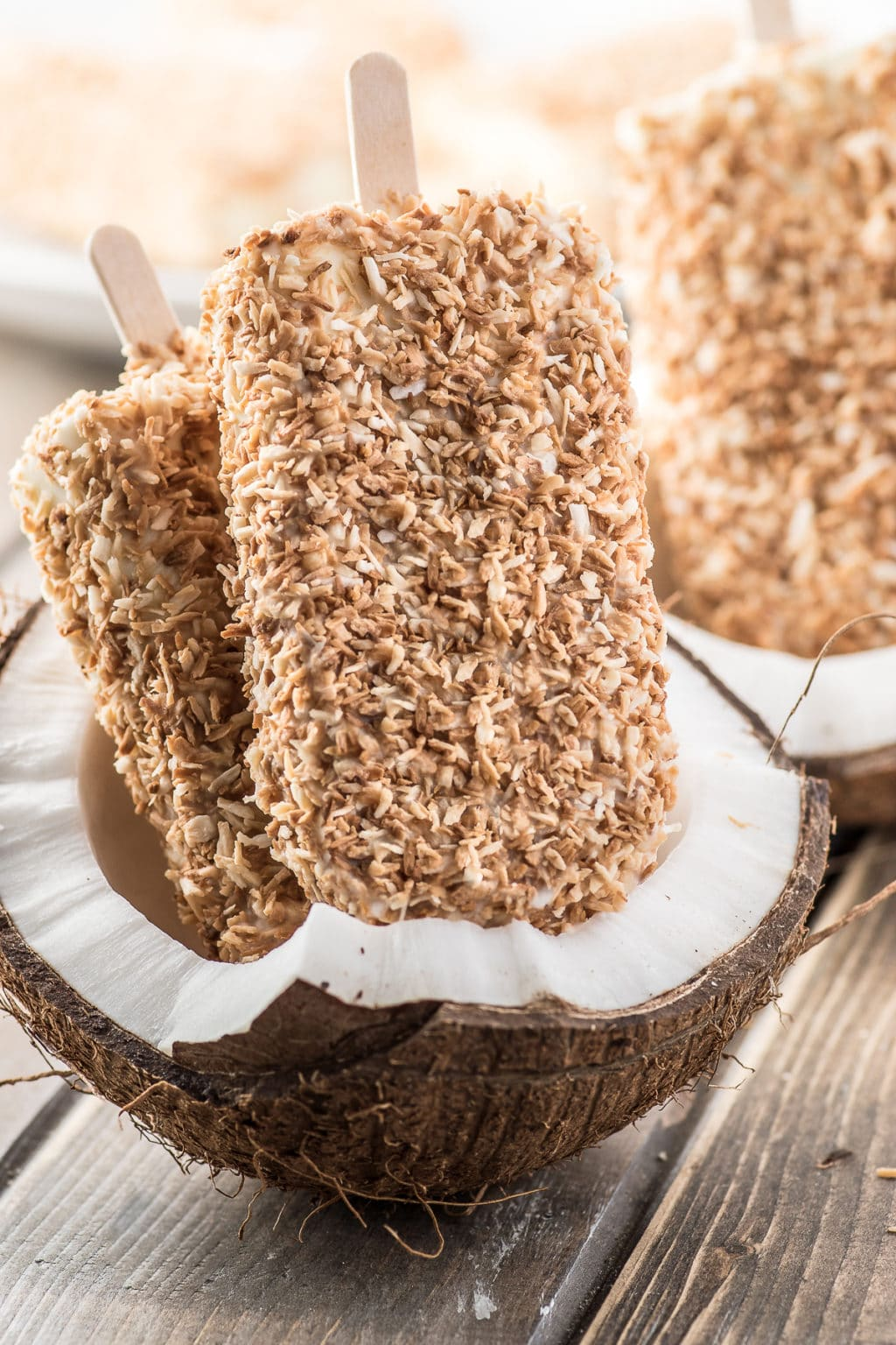 Toasted coconut cream popsicles displayed inside of a cracked fresh coconut
