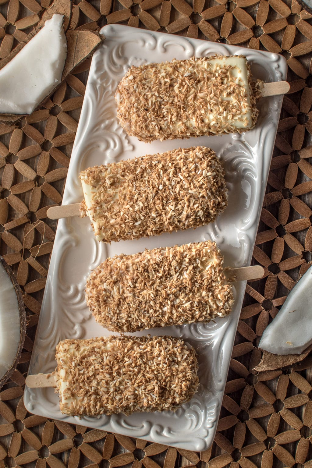 overhead shot of creamy coconut ice cream bars coated in toasted coconut resting on a white plate on a textured wood background