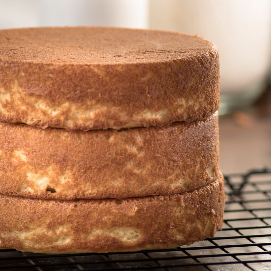 Three golden brown cake layers stacked on top of one another on a black wire cooling rack.