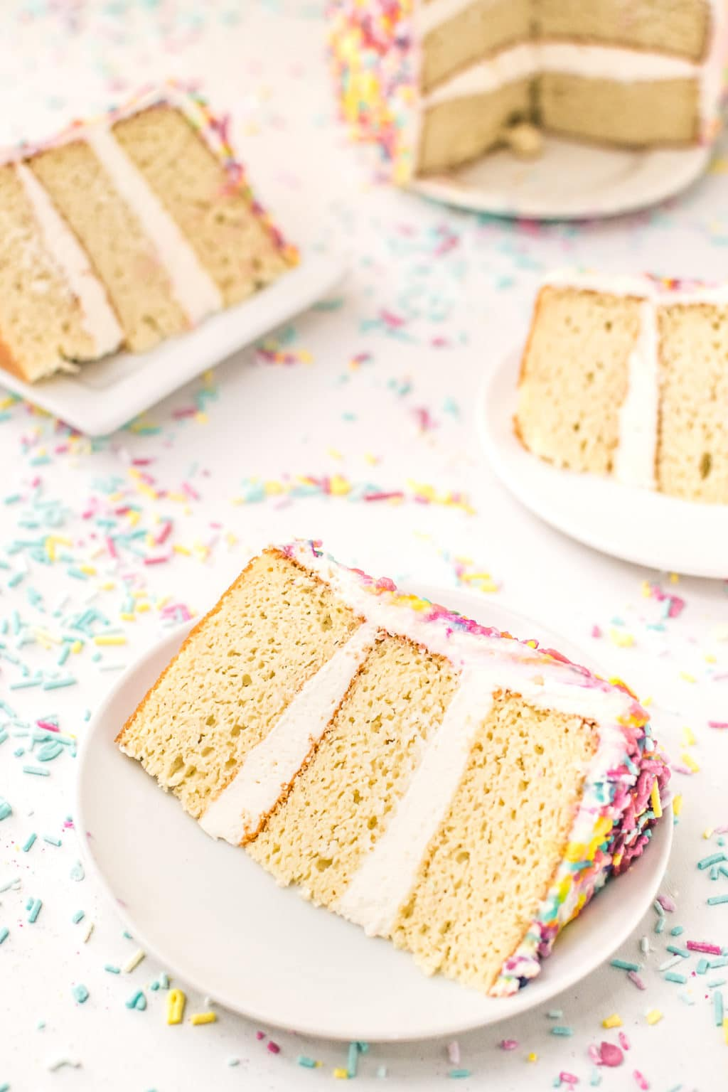 Slices of low carb birthday cake with white icing surrounded by sprinkles