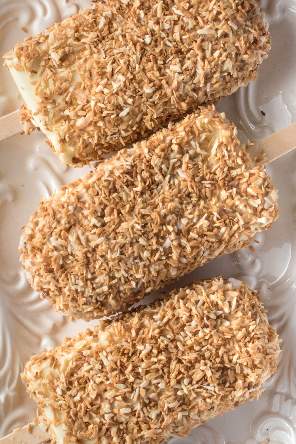homemade coconut ice cream bars coated in toasted coconut resting on a white textured plate.