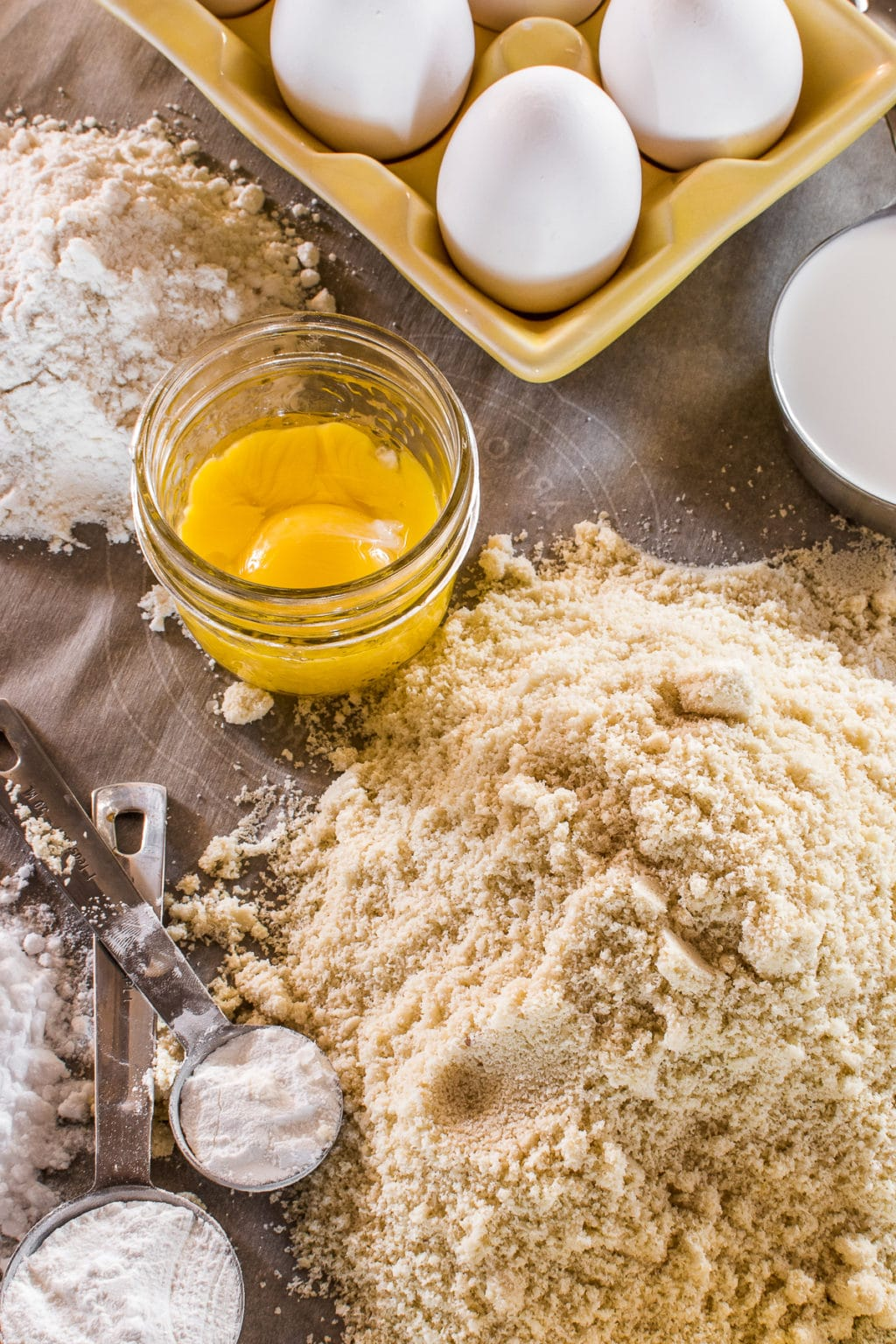A table of baking ingredients with flours, eggs, and measuring spoons