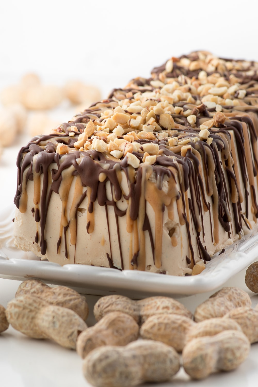 ice cream cake on a plate drizzled with peanut butter and chocolate topped with chopped peanuts