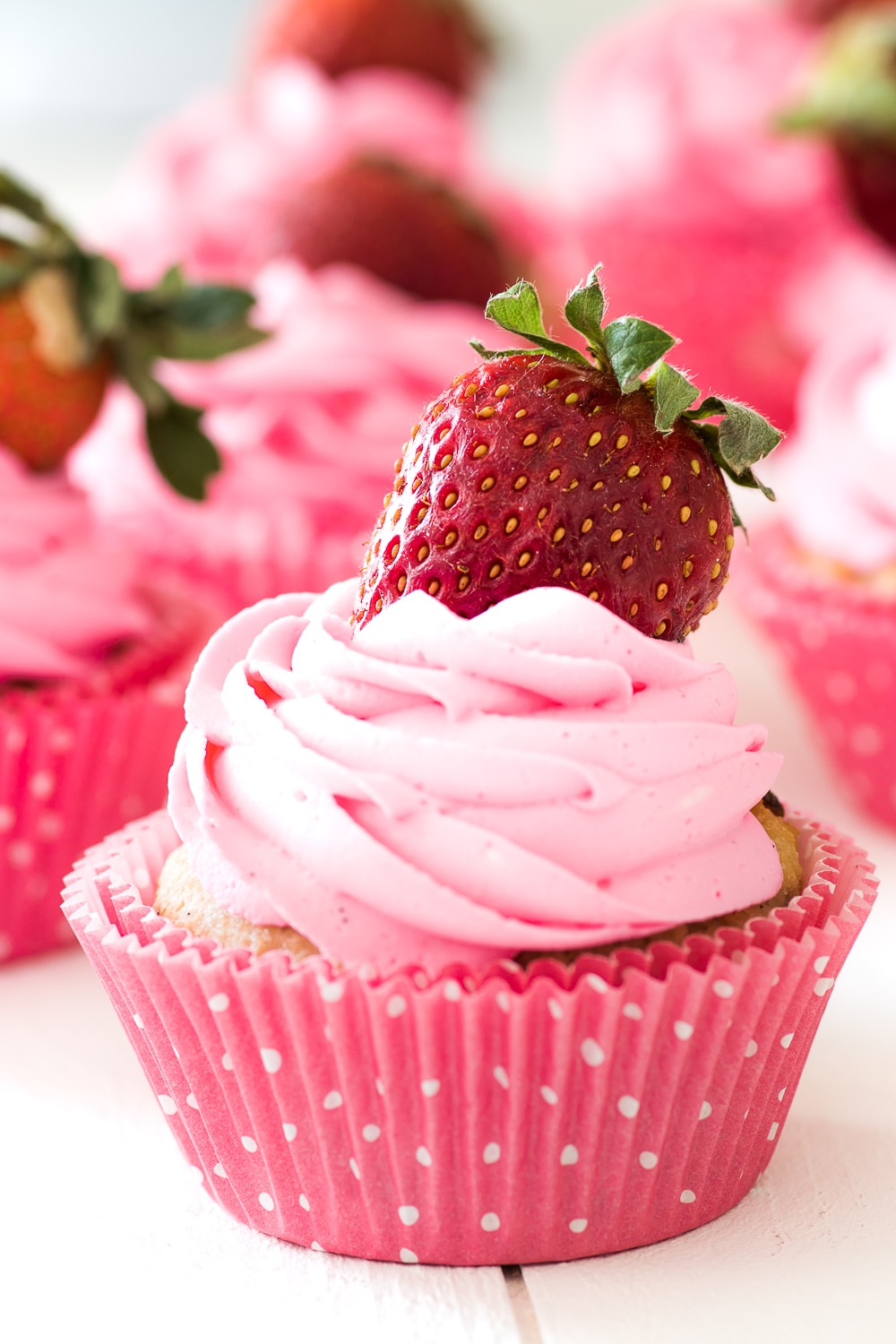Pink strawberry cupcakes with pink icing and a bright red strawberry on top