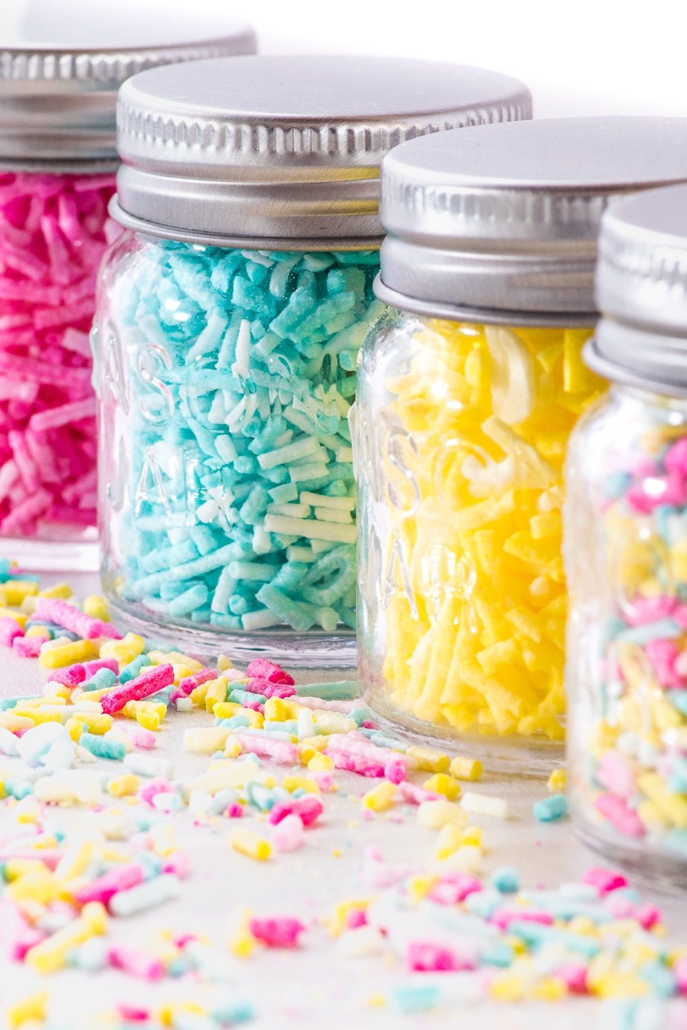 Small glass jars filled with colorful sprinkles.  Sprinkles are also coating the bright white tabletop.