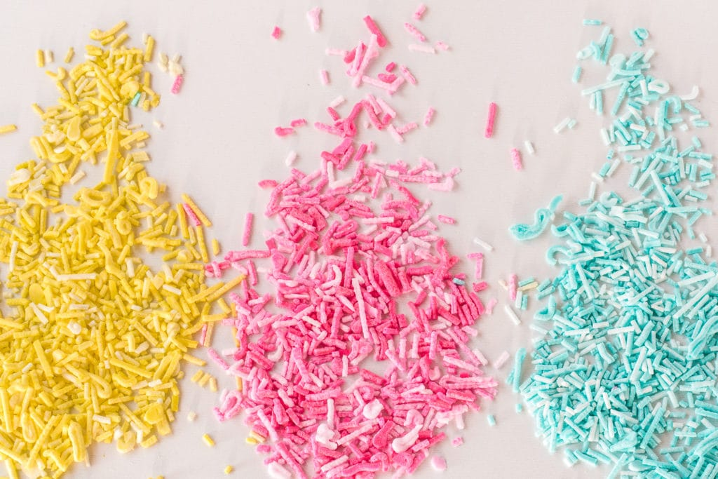 yellow, pink and blue sugar-free sprinkles spread on a white background