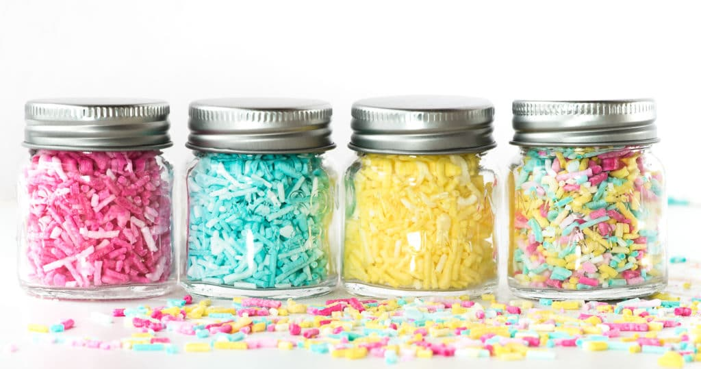 Four jars in a row filled with colourful ombre sprinkles