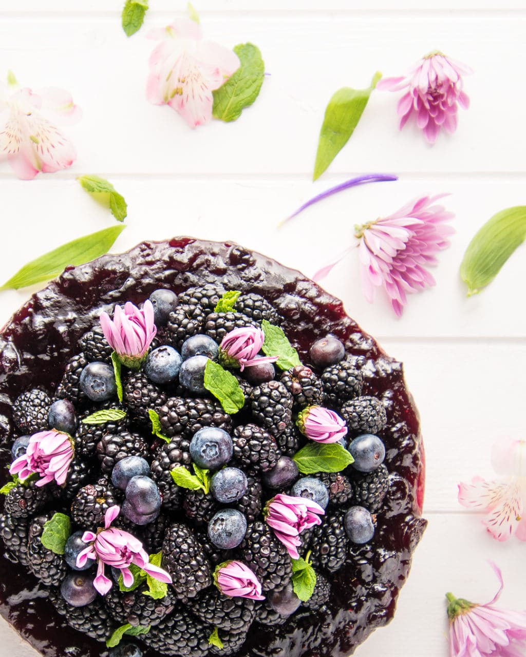 Overhead photograph of a berry cheesecake with sprigs of mint and pink flowers