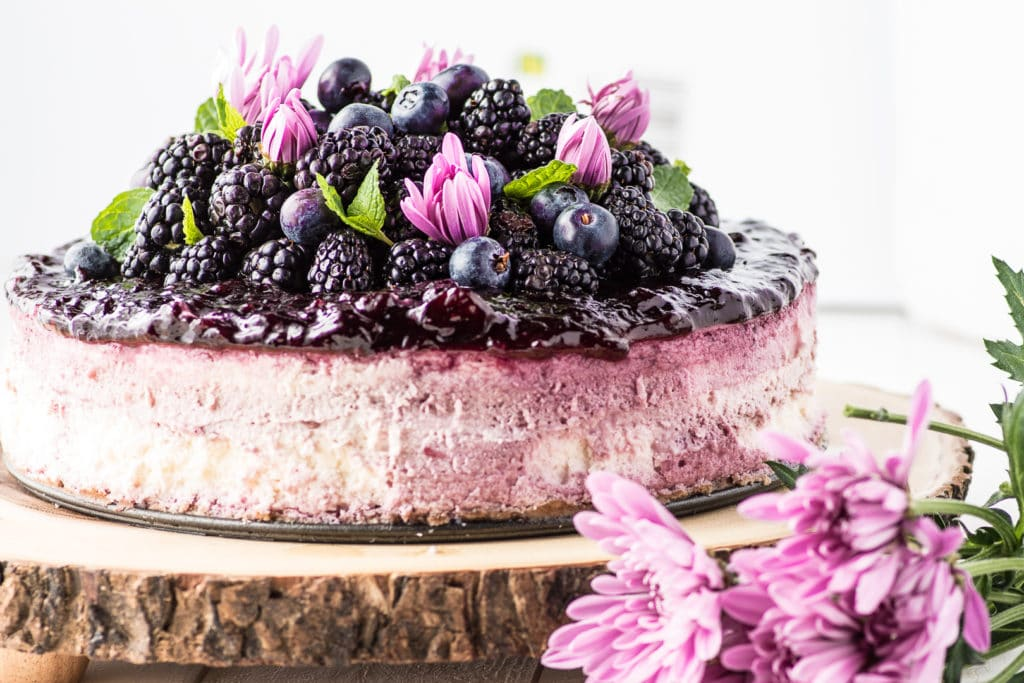 A blackberry cheesecake topped with fresh berries on a rustic wooden slab