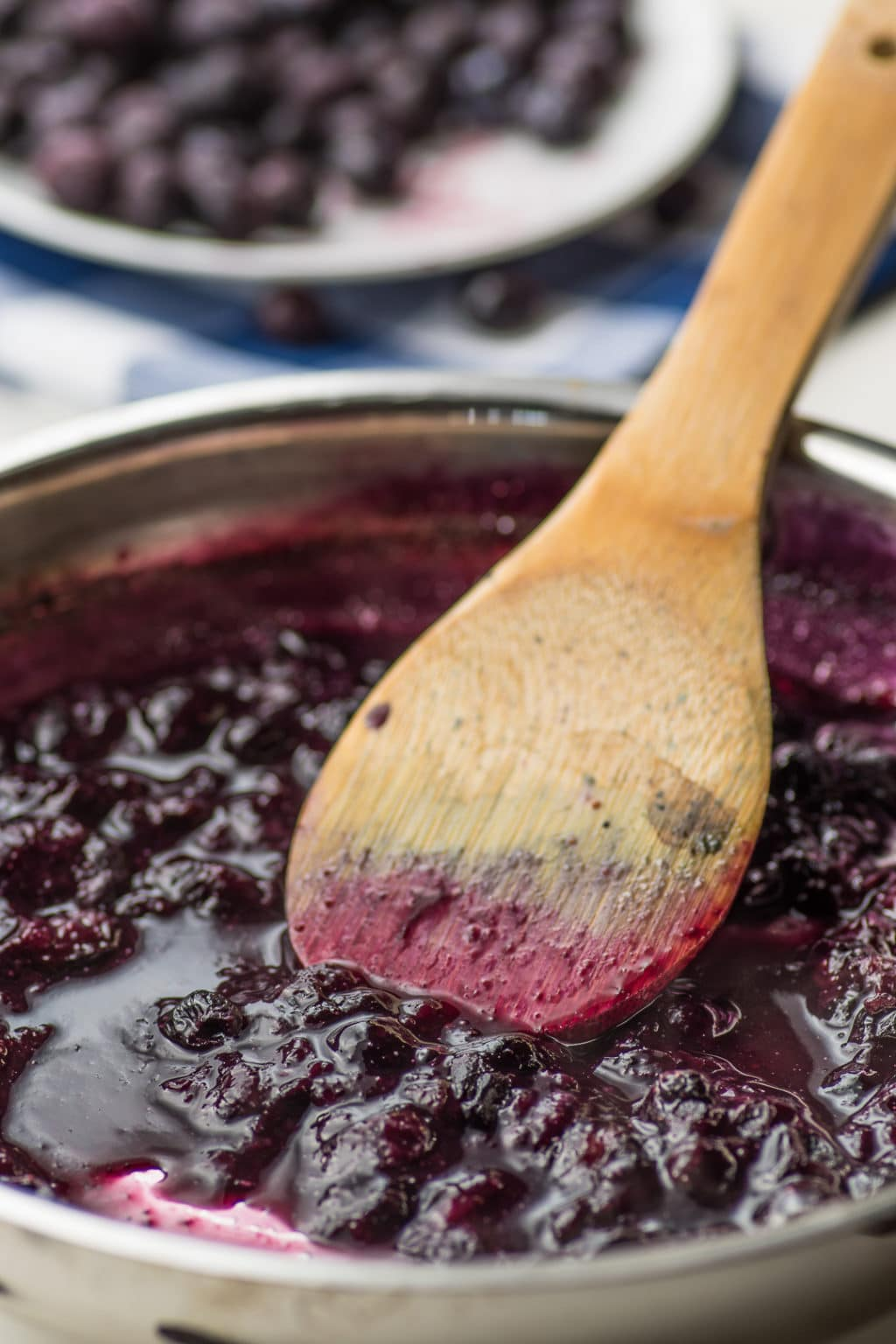 A silver sauce pan with cooked blueberries and a wooden spoon
