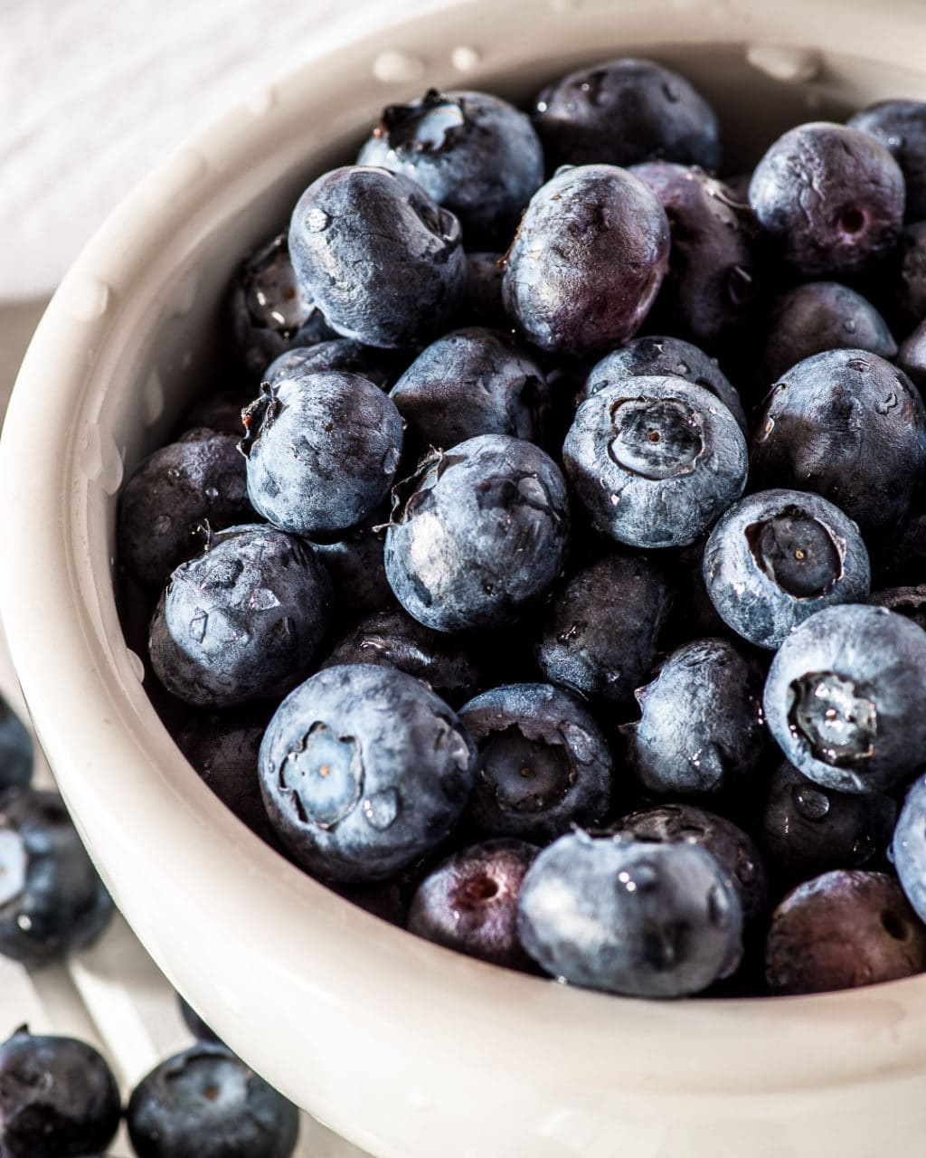 a white bowl filled with fresh blueberries