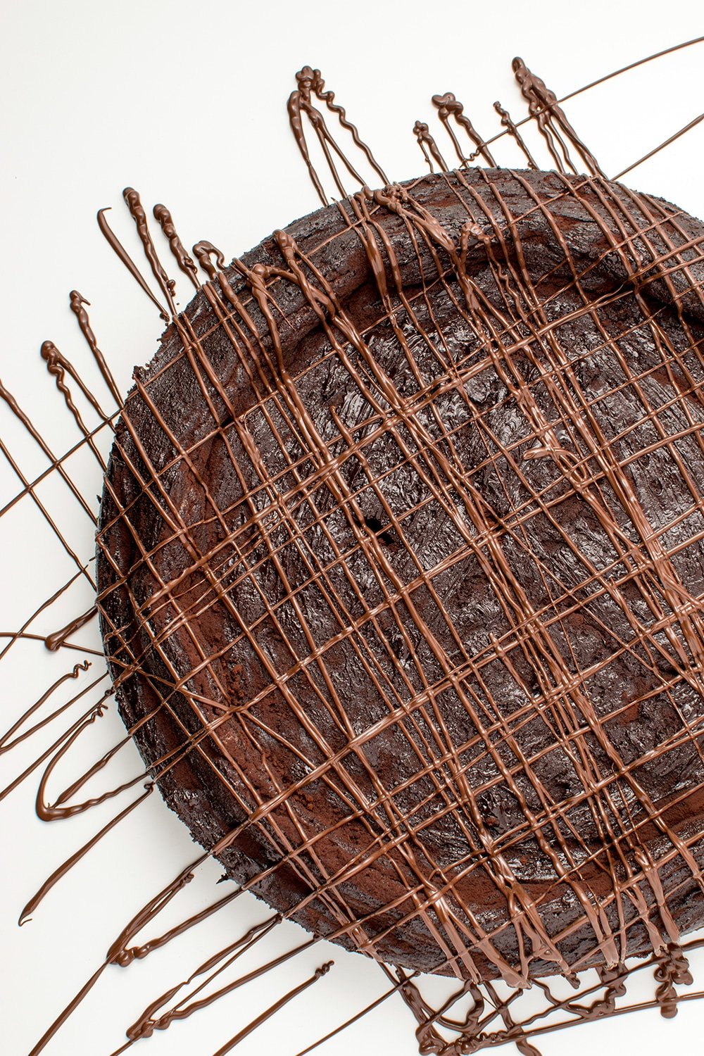 chocolate torte covered in stripes of melted chocolate on a white background