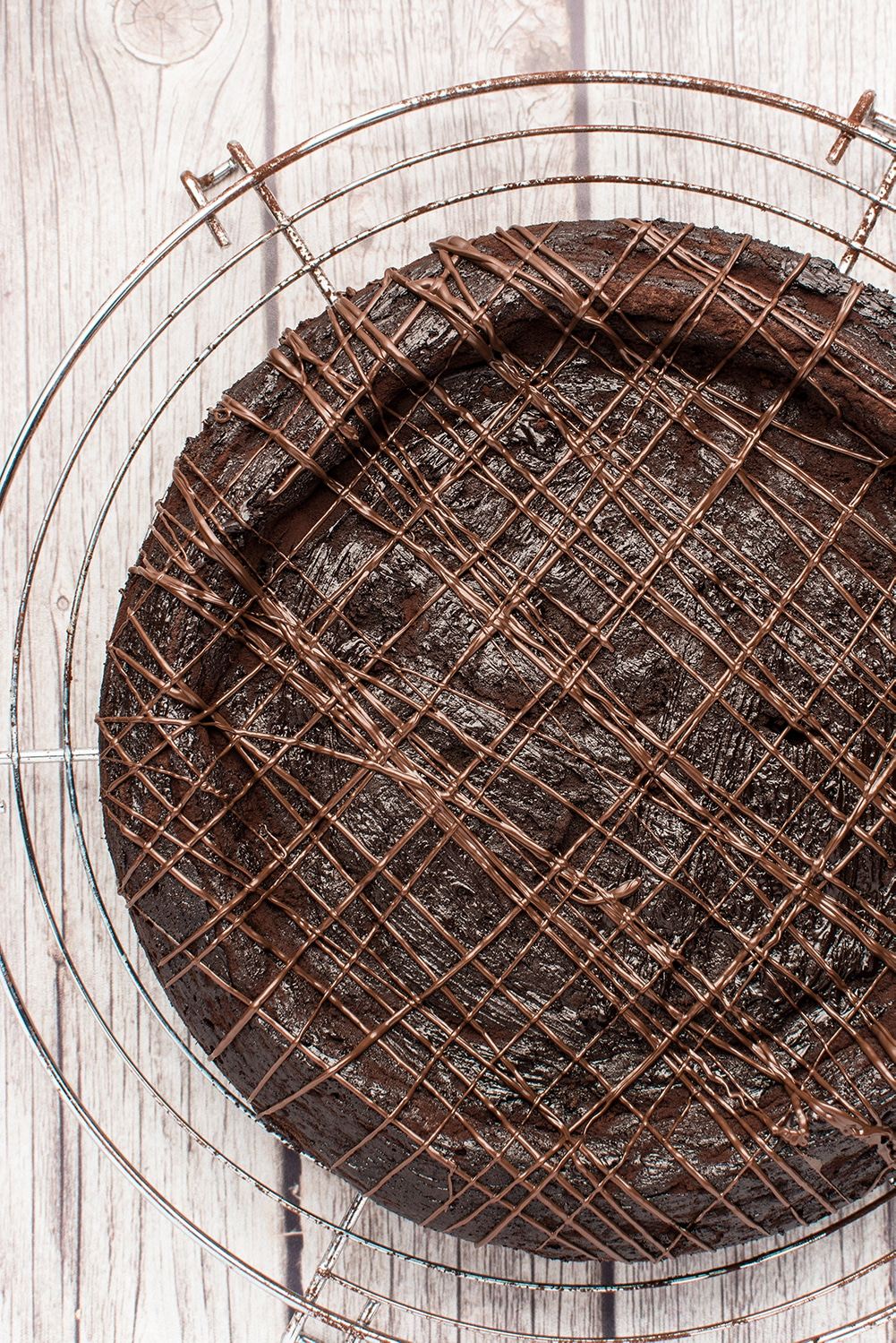 dark chocolate torte with stripes of melted chocolate resting on a round metal cooling rack