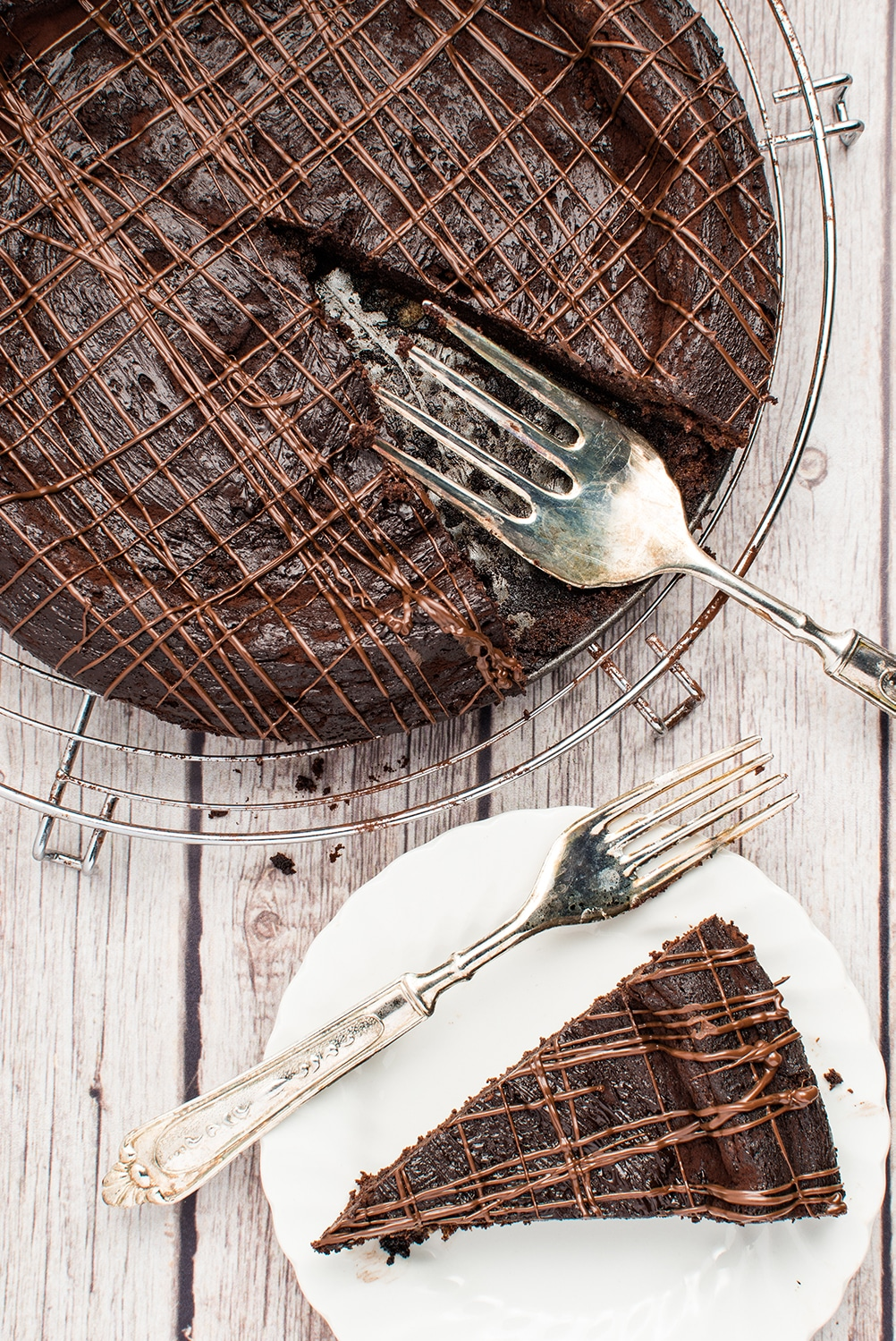 Chocolate torte on a metal cooling rack with a piece removed and placed on a small white plate