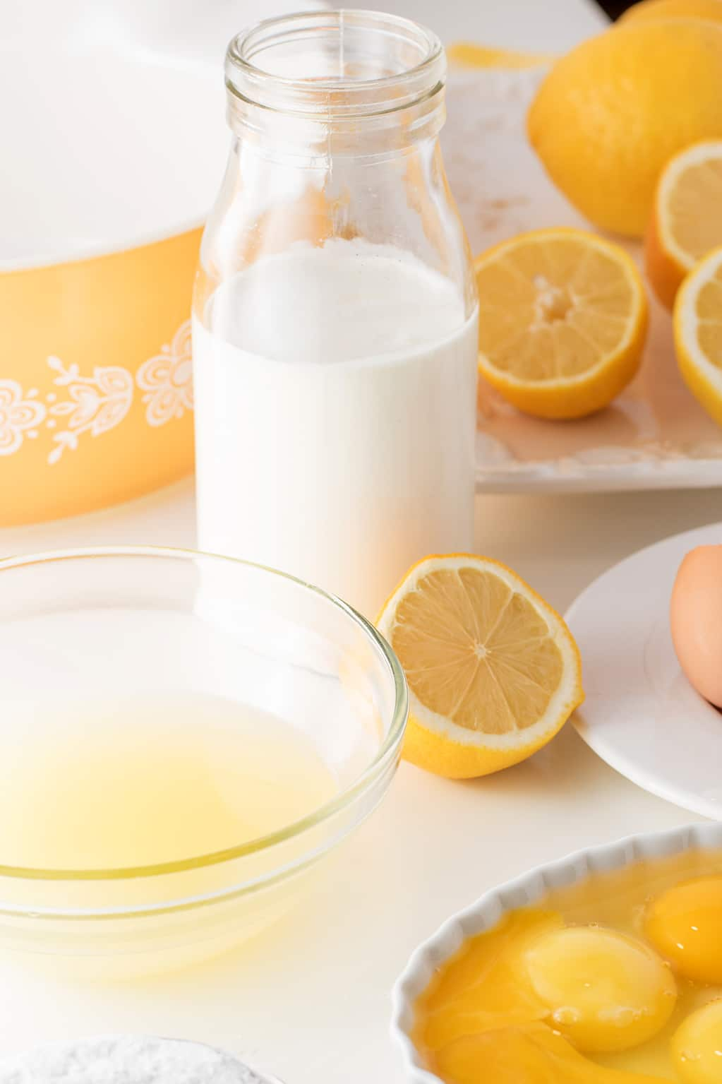 lemons, cream, egg whites and egg yolks on a white background