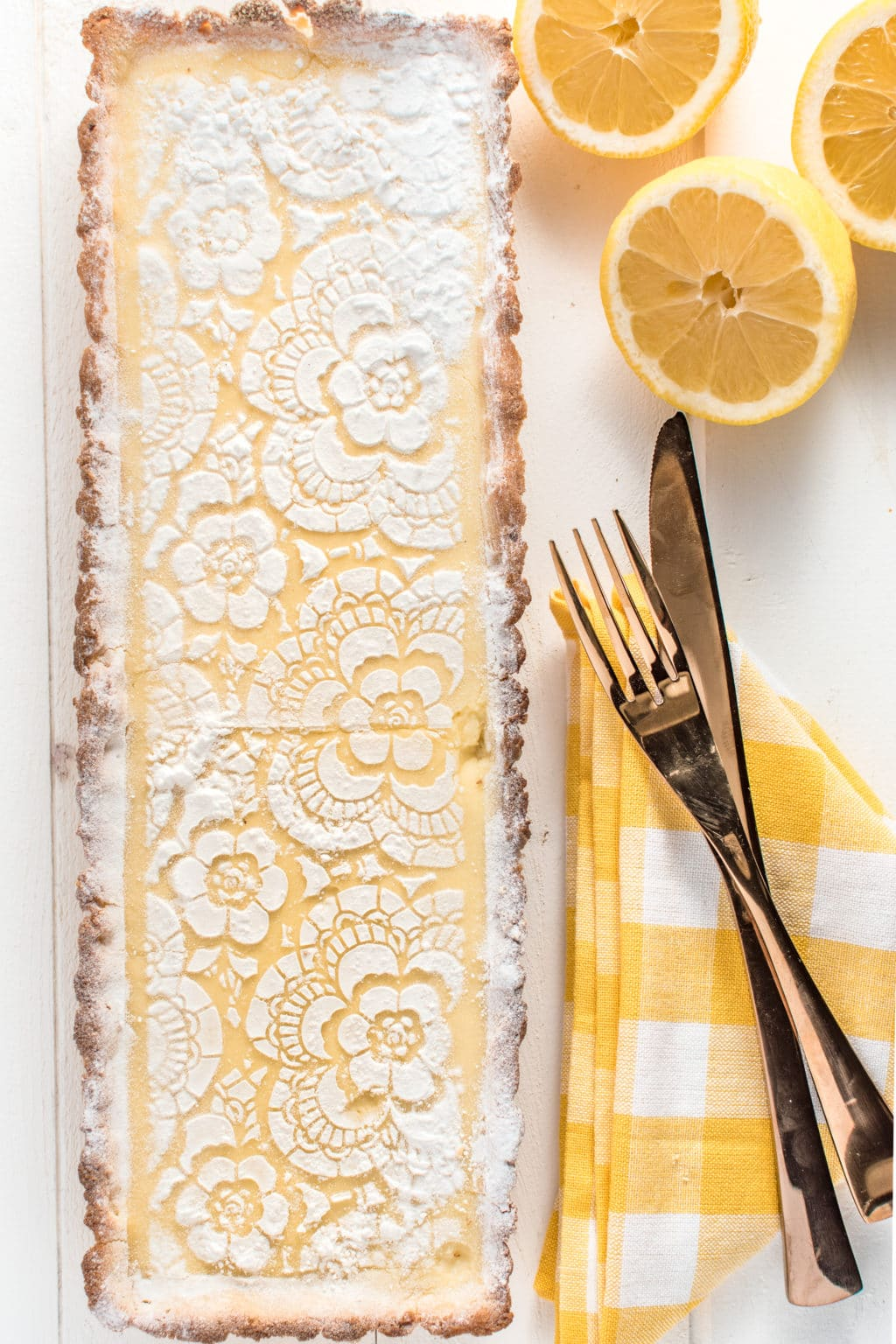 a top down photo of a rectangular lemon tart, with a gingham yellow napkin and fresh lemons on a white wooden background