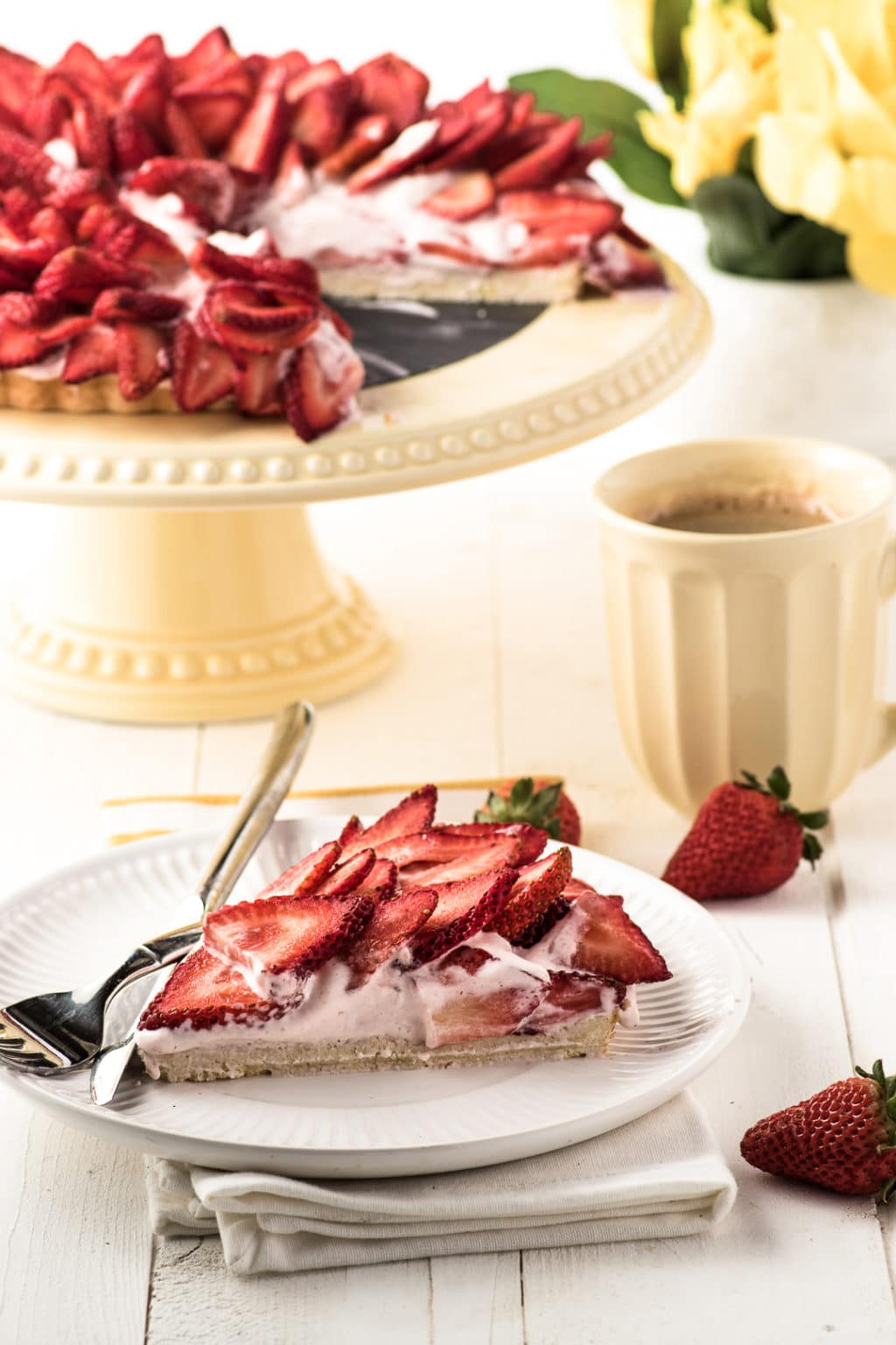 A strawberry cream pie topped with sliced strawberries on a yellow cake stand