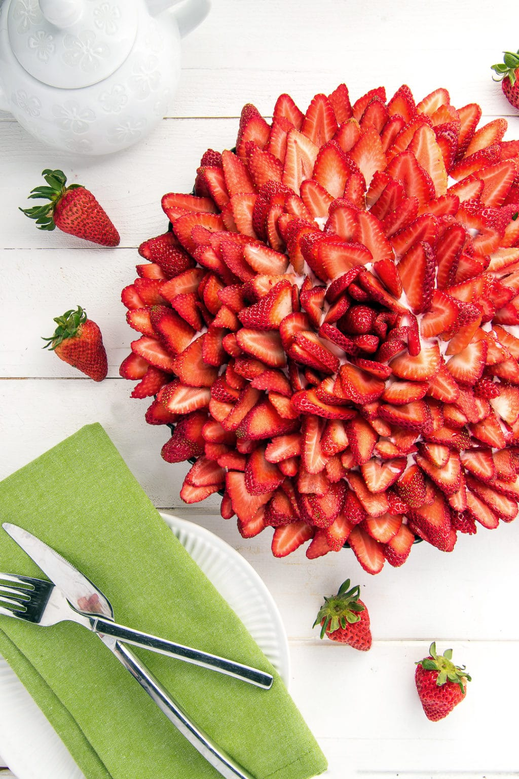 A strawberry cream pie topped with sliced strawberries. The strawberries are arranged in a rose pattern.
