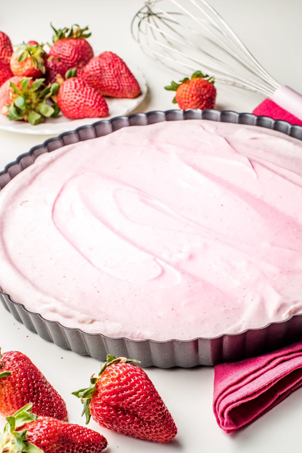 Strawberry cream pie filling inside of a tart pan surrounded by fresh strawberries