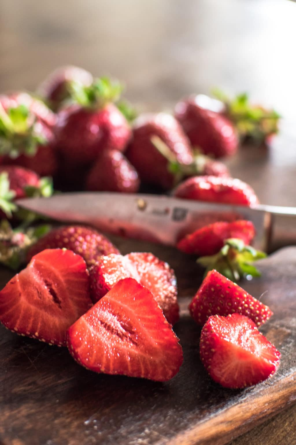 a close up shot of ripe sliced strawberries on a wooden cutting board