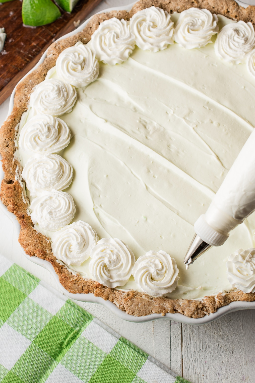 A key lime pie with whipped cream piped rosettes on a white background with green napkins and slices of lime