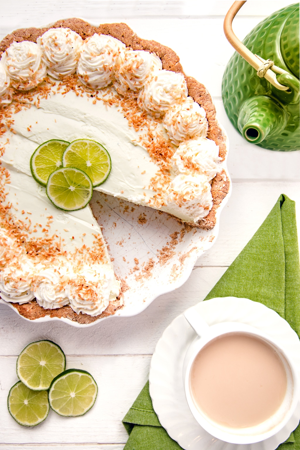 A no bake key lime pie with a slice removed on a white background with green napkins, sliced limes and bright green tea pot