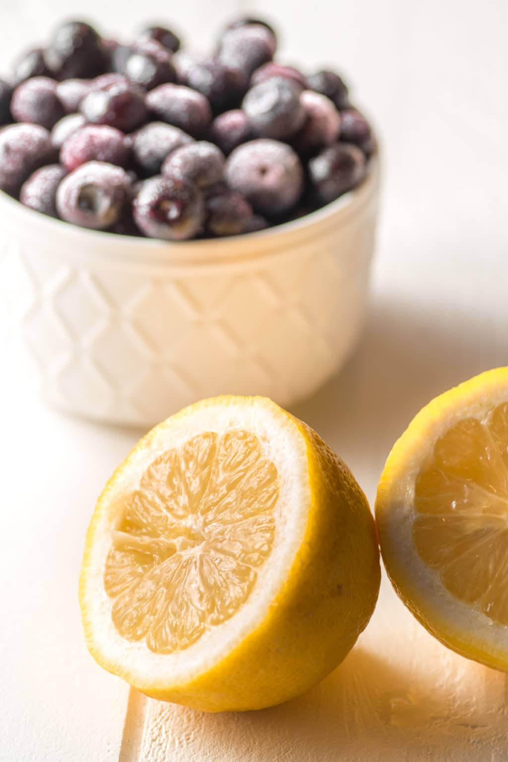 A bowl of frozen blueberries in a textured white bowl with a slice fresh lemon in the foreground.