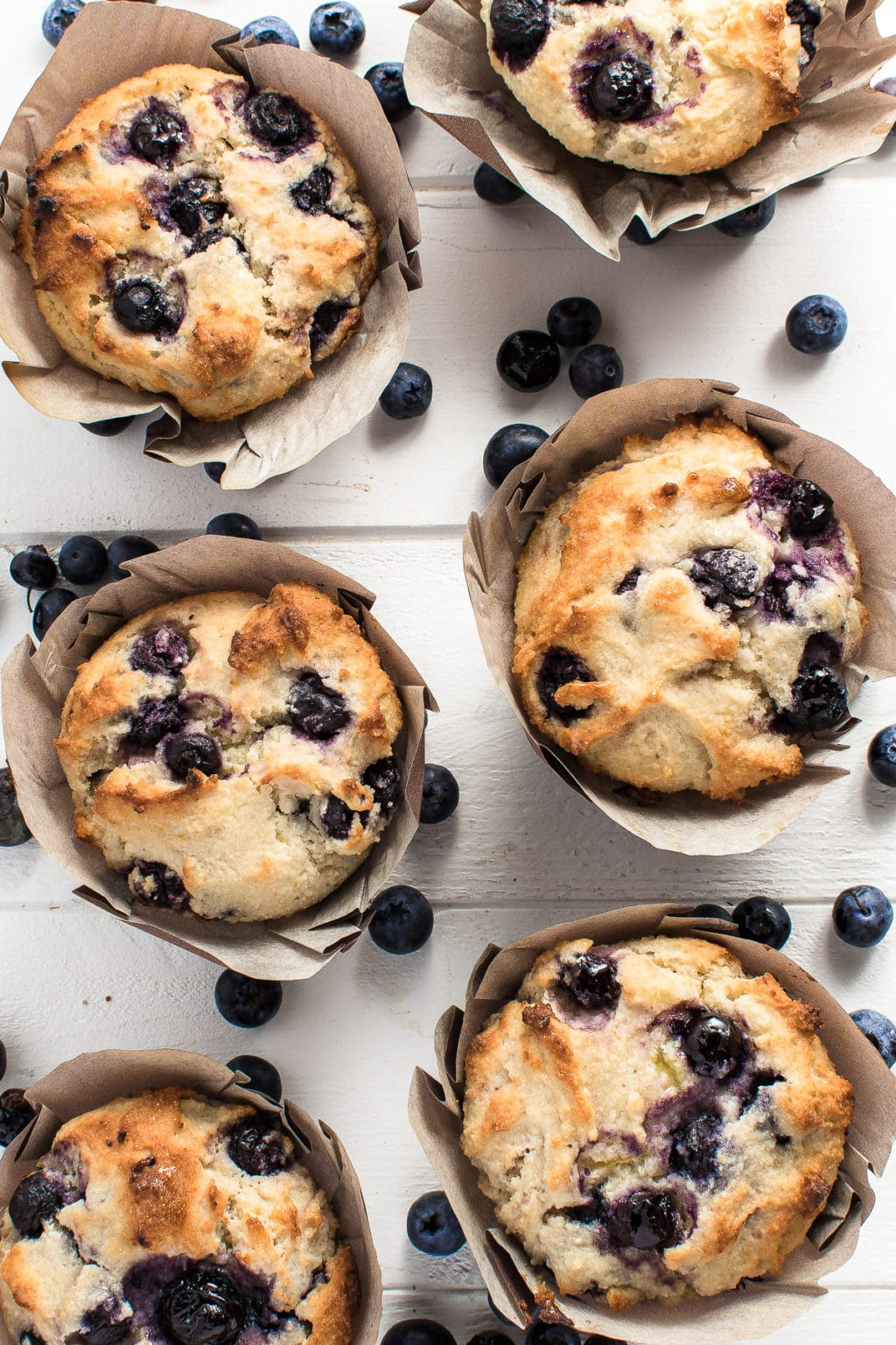 Blueberry muffins on a bright white wooden background with scattered fresh blueberries
