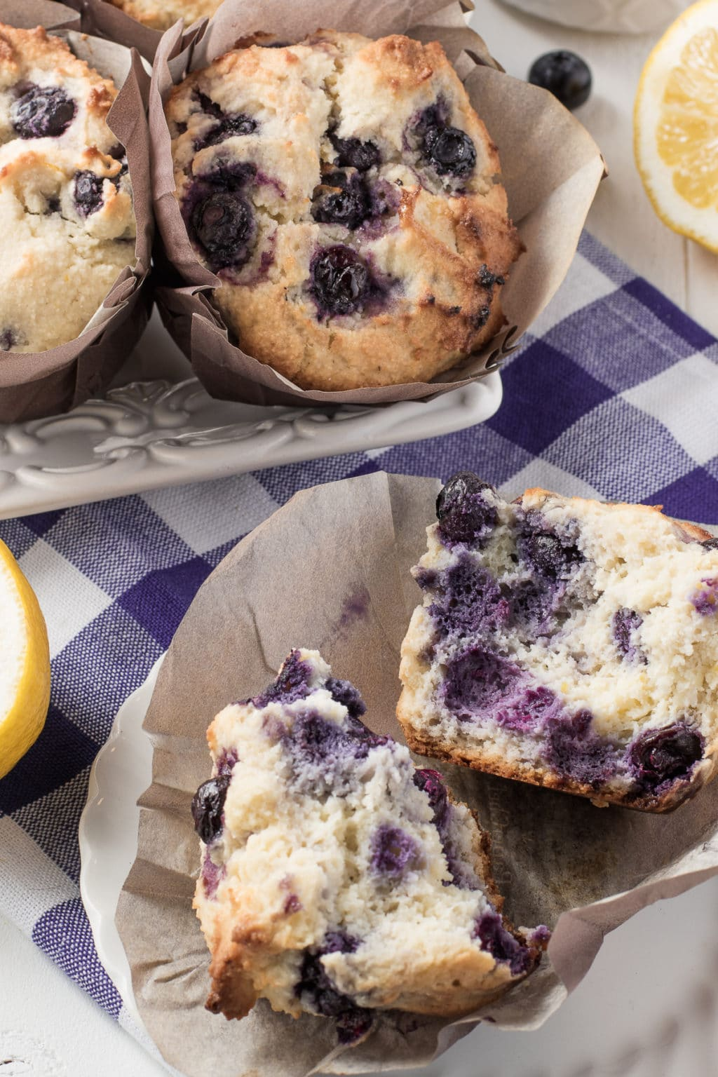 A fresh gluten-free blueberry muffin split down the centre resting in a muffin liner. Surrounded by fresh blueberry muffins and lemons all on a bright blue gingham napkin