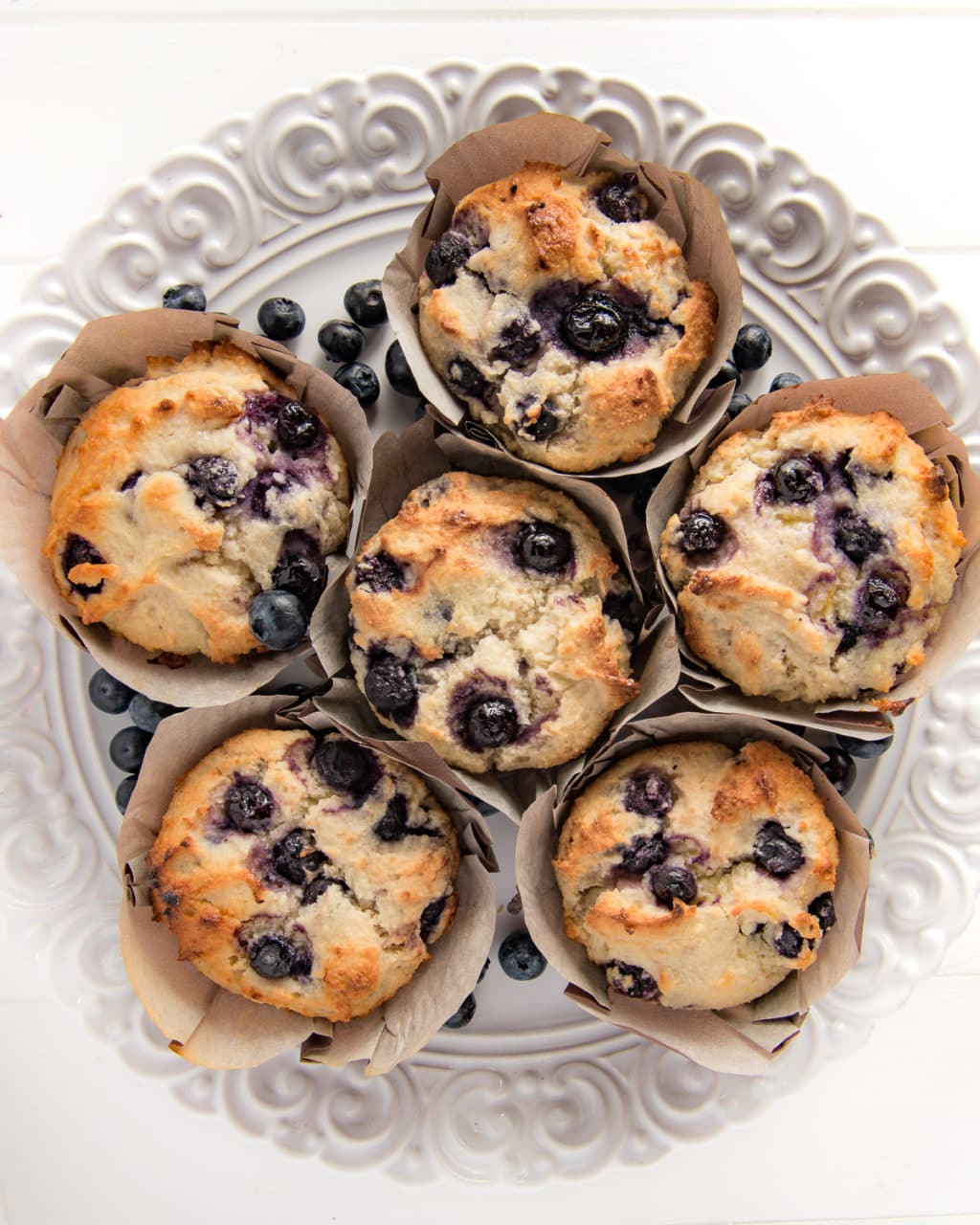 A top down shot of low carb blueberry muffins in muffin wrappers laid out on a textured bright white plate.