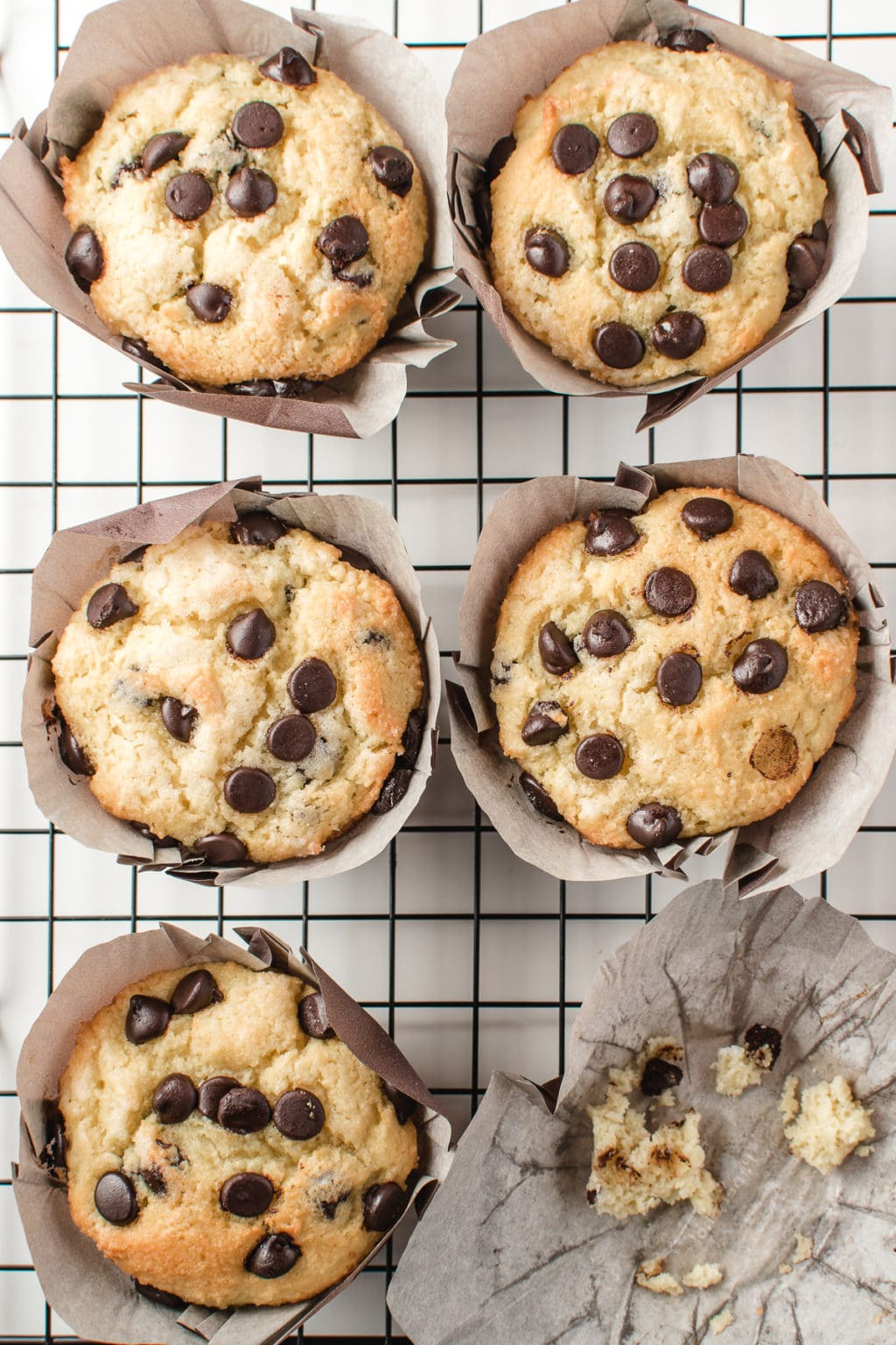 6 bakery style chocolate chip muffins on a black grid cooling rack with one muffin missing leaving only crumbs behind.