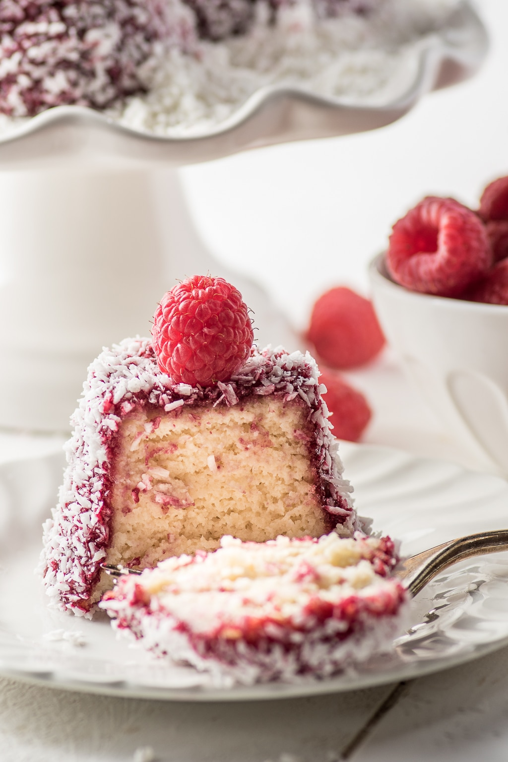A sliced raspberry coconut english madeleine cake on a white plate