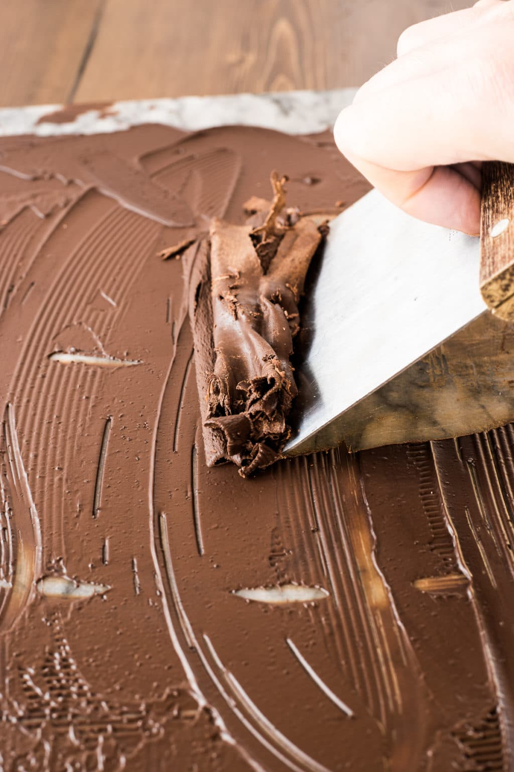 Melted chocolate on a marble board being pushed with a pastry scraper to create large flakes and ribbons of dark chocolate
