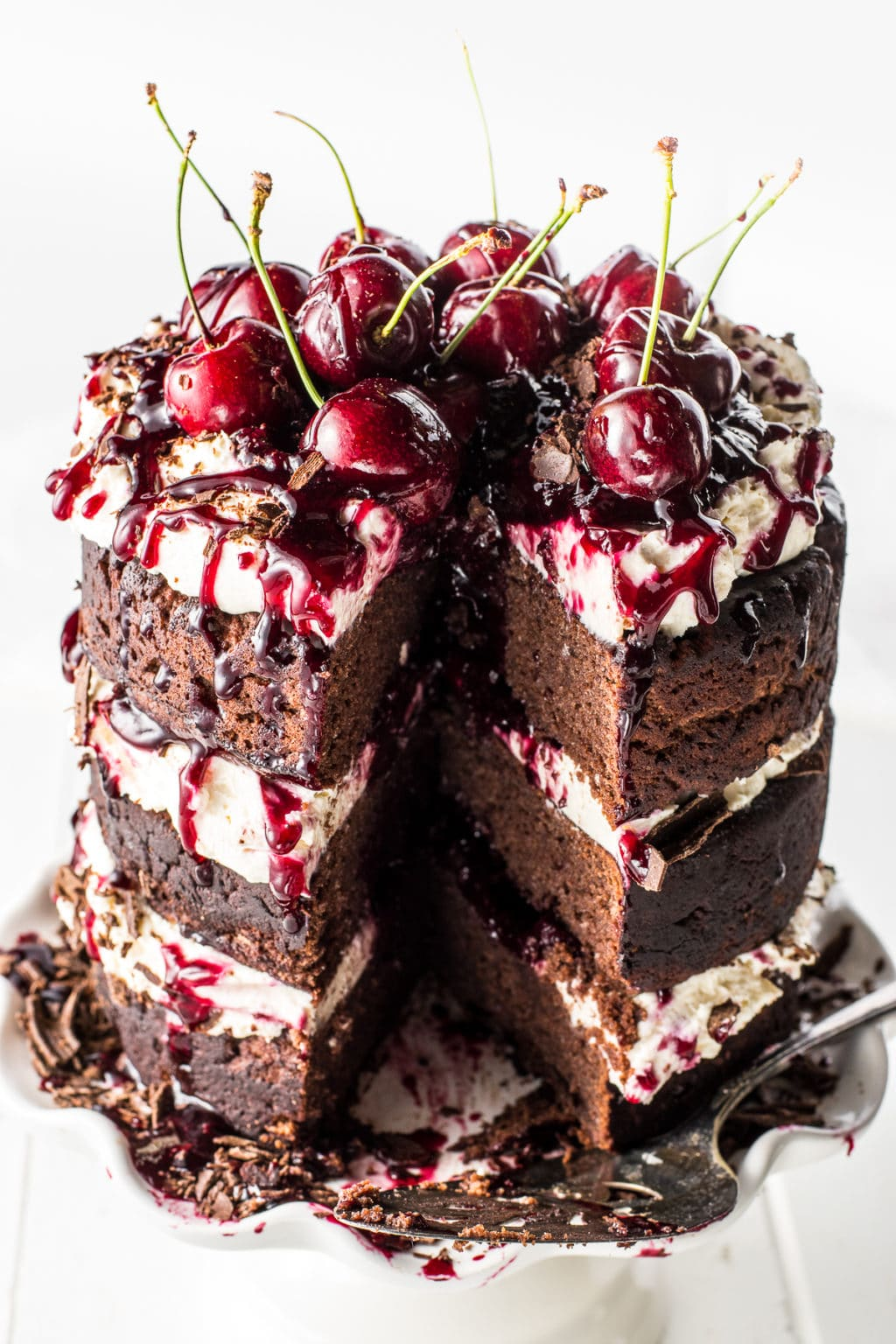 A gluten free black forest cake with a slice removed against a bright white background and wooden table