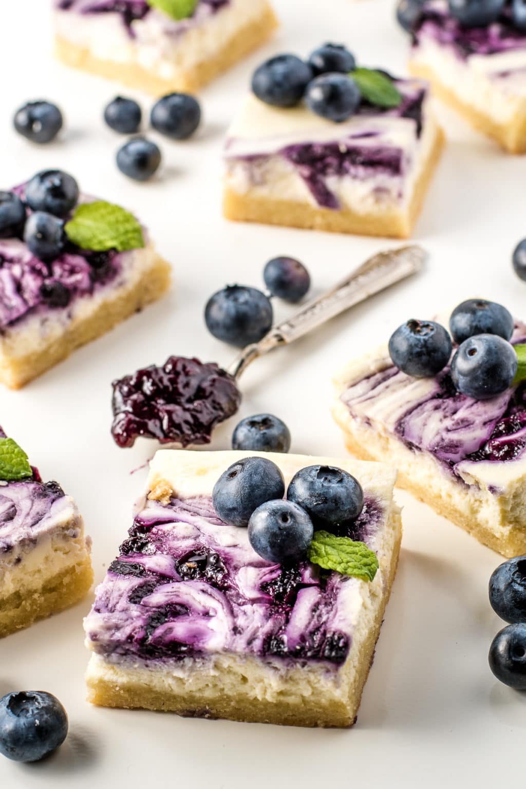 Blueberry cheesecake bars topped with swirls of pureed blueberries, fresh blueberries, and sprigs of mint