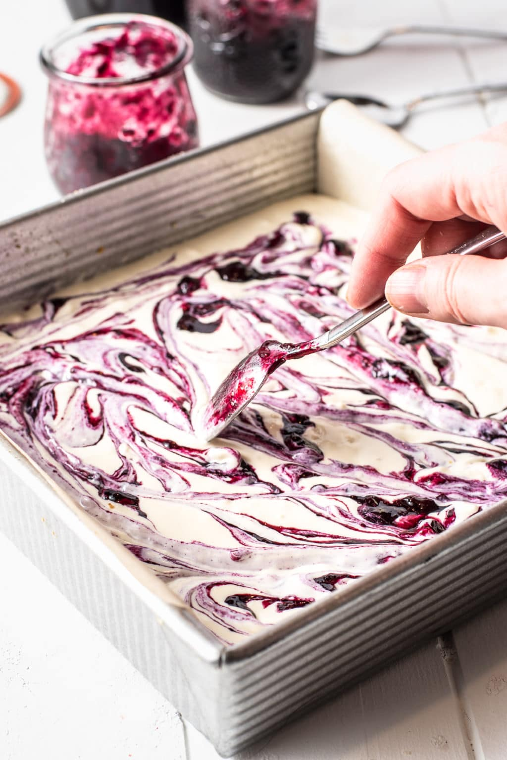 A spoon swirling bright purple blueberry puree through cheesecake batter
