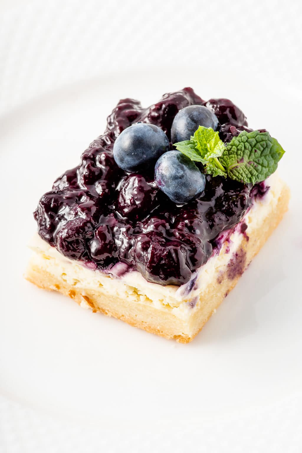 Cheesecake bars topped with blueberry jam and fresh blueberries