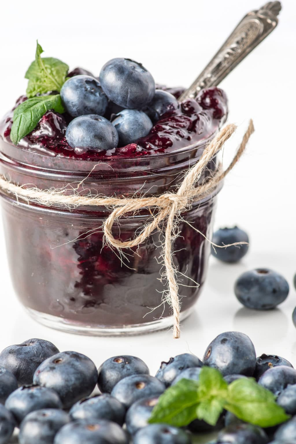 Small jar of sugar-free blueberry jam with a piece of twine wrapped around the top tied into a bow.