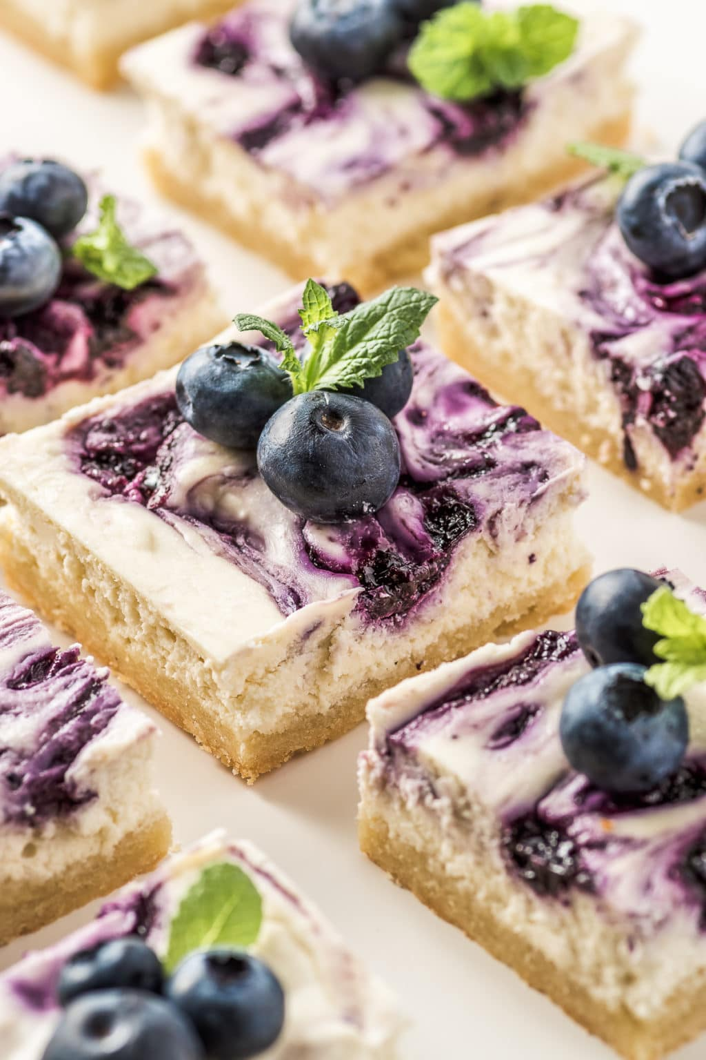 Close-up photo of keto blueberry cheesecake bars set on a white plate. They are topped with fresh blueberries and mint sprigs.