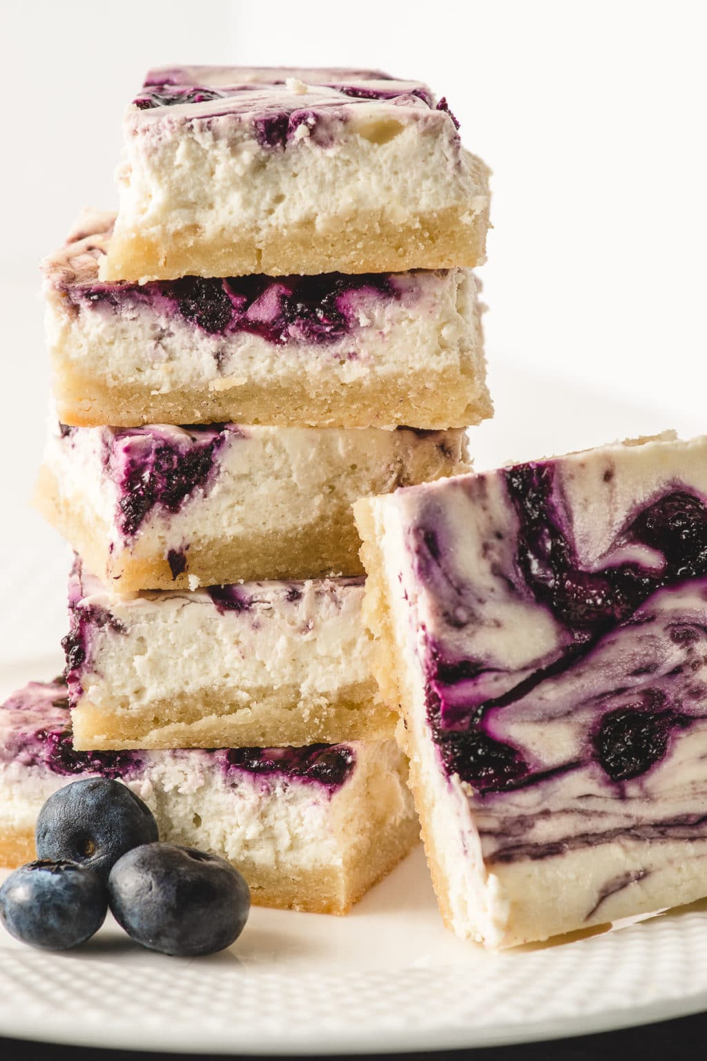 On a white, textured plate is a stack of creamy, sugar-free, blueberry cheesecake bars. A few scattered, fresh blueberries are piled in front of the bars.