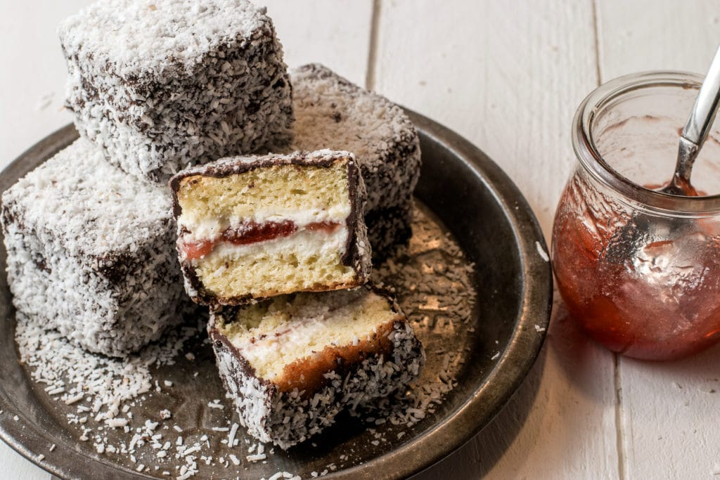 Gluten-free jam filled lamingtons on a rustic pie tin with a jar of strawberry jam.