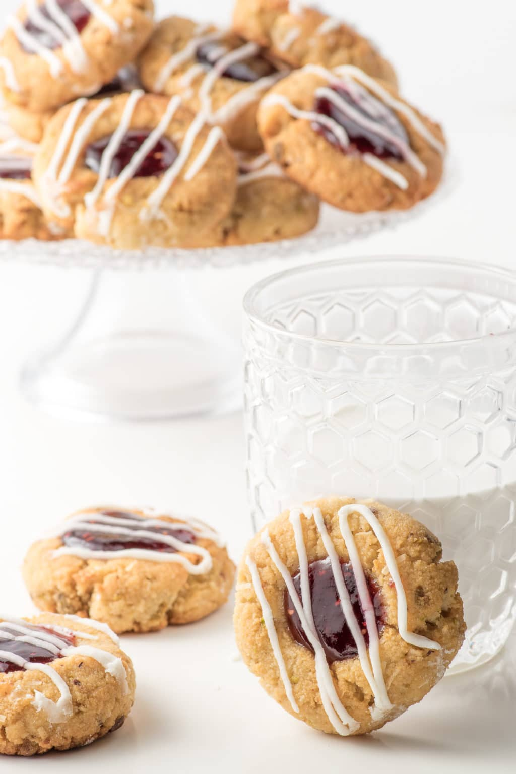 Set on a white backdrop are three, almond flour thumbprint cookies in the foreground, with one propped against a glass half filled with milk. The background contains a blurred, pedestal cake plate piled with raspberry jam-filled, almond flour, thumbprint cookies with pistachios.  All cookies are drizzled with white icing.