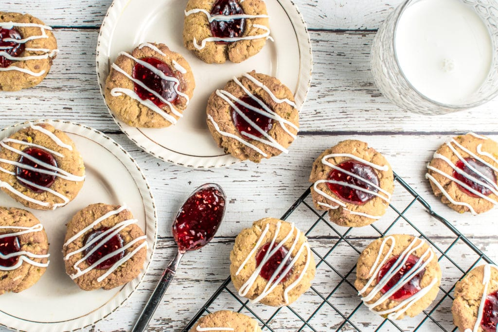 Keto raspberry jam thumbprint cookies on two, ivory, vintage dessert plates set on a rustic white barnyard backdrop. A glass of milk and a cooling rack with more cookies, along with a teaspoon filled with gooey, raspberry jam, complete the picture.