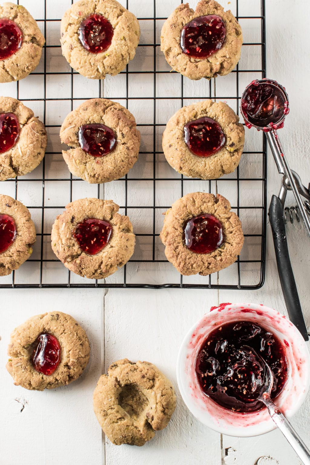 Set on a white backdrop, are nine thumbprint cookies filled with gooey, raspberry jam spaced evenly on a cooling rack. A stainless cookie scoop, half full of sticky jam, rests on the right side of the metal rack.  Below the rack, are two cookies--one filled with jam, and one with an empty divot. Beside the empty cookie is a jam-filled teaspoon inside a small, white bowl filled with sticky, raspberry jam.