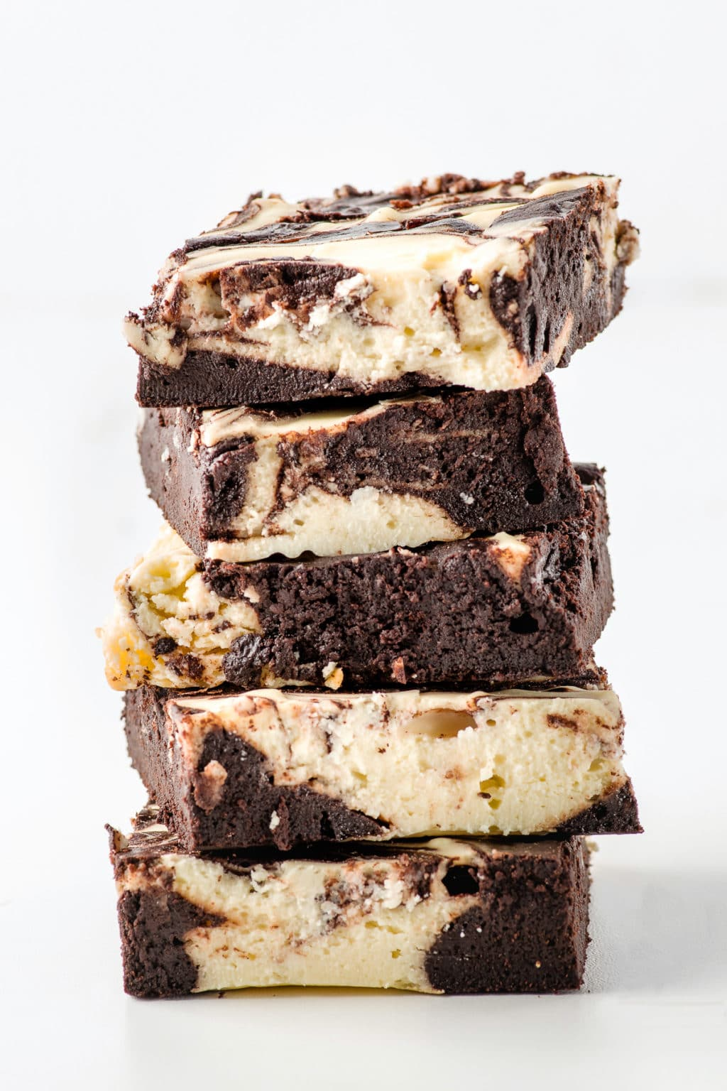 A stack of keto cheesecake brownies against a bright white background.